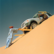 Tuareg Tribesman using sand-ladders to aid a 4x4 vehicle over the crest of a dune in the Sahara desert, Libya
