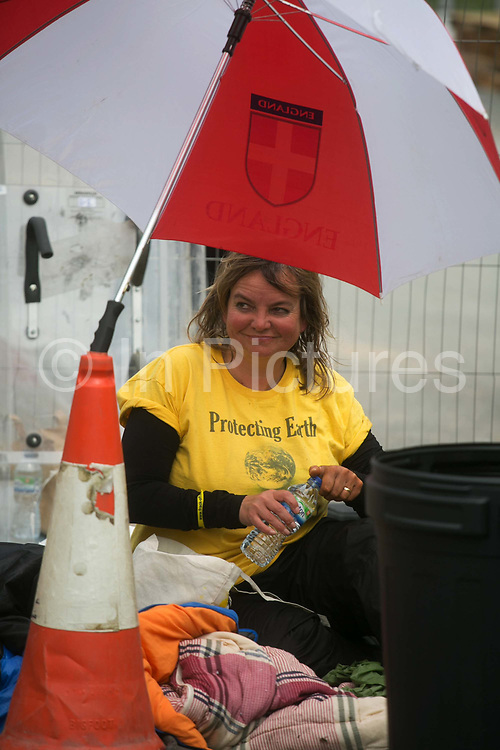 12 local activists locked themselves in specially made arm tubes to block the entrance to Quadrillas drill site in New Preston Road, July 03 2017, Lancashire, United Kingdom. Councillor Miranda Cox sits up for the first time in 10 hours after having been cut loose.The 13 activists included 3 councillors; Julie Brickles, Miranda Cox and Gina Dowding and Nick Danby, Martin Porter, Jeanette Porter,  Michelle Martin, Louise Robinson,<br /> Alana McCullough, Nick Sheldrick, Cath Robinson, Barbara Cookson, Dan Huxley-Blyth. The blockade is a repsonse to the emmidiate drilling for shale gas, fracking, by the fracking company Quadrilla. Lancashire voted against permitting fracking but was over ruled by the conservative central Government. All the activists have been active in the struggle against fracking for years but this is their first direct action of peacefull protesting. Fracking is a highly contested way of extracting gas, it is risky to extract and damaging to the environment and is banned in parts of Europe . Lancashire has in the past experienced earth quakes blamed on fracking.