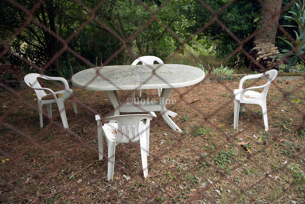 plastic garden furniture placed behind rusty fence in the garden
