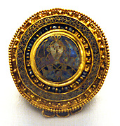 The Castellani brooch. This gold disc brooch is decorated in cloisonné enamel and pearls. The rings at the base are for three pendants. The central image depicts a human bust between stylized cypress tress. The enamels, now faded, included red, blue and green.