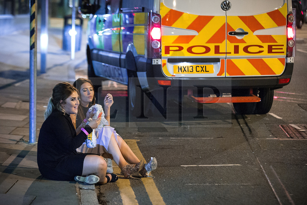 © Licensed to London News Pictures . 01/11/2015 . Manchester , UK . Two women sit in the gutter and eat a takeaway . Halloween revellers , wearing make up and costumes , out and about in Manchester City Centre . Photo credit : Joel Goodman/LNP