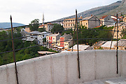 The busy old market bazaar street Kujundziluk with lots of tourist craft and art shops and street merchants. Restaurants cafes along the river. Seen from the old bridge through the bridge iron railing. Historic town of Mostar. Federation Bosne i Hercegovine. Bosnia Herzegovina, Europe.
