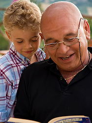 Close up of grandad reading book to grandchild