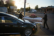Jorge Ortiz, general manager of Perches Funeral Homes,  pushes a casket to a hearse with Assistant Funeral Director Gabriel Tavarez at Perches Funeral Home - Central in El Paso, Texas, U.S., on December 4, 2020. Funeral homes in El Paso have been receiving an unprecedented wave of COVID-19 related deaths in the last months.