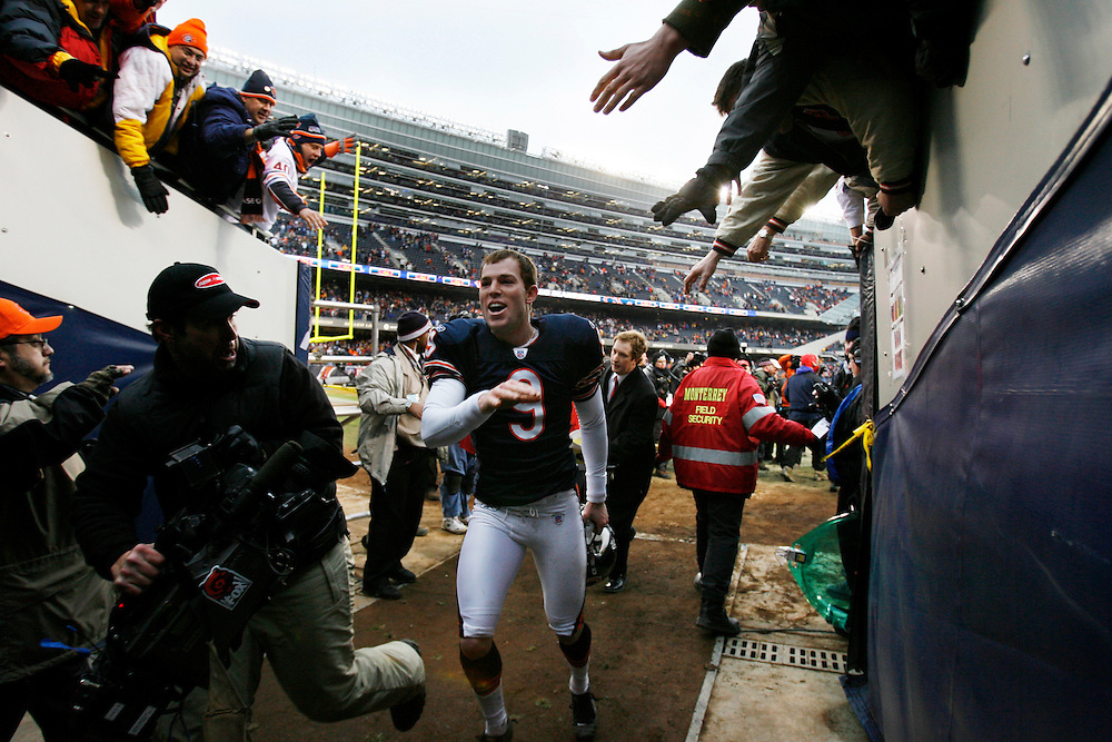 Chicago's Robbie Gould (9) celebrates with fans as he runs through the tunnel back to the locker room after kicking the game-winning field goal in the overtime period.  .