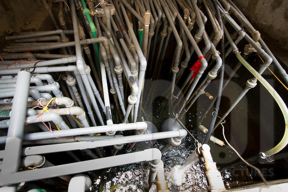 Concrete water tank where hundreds of PVC plumbing pour out liters of liquid. Hanoi, Vietnam, Asia
