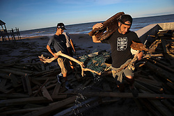 October 8, 2016 - Vilano Beach, Florida, U.S. - WILL VRAGOVIC   |   Times.Nate Higgins, right, and his nephew, Quinn, carry driftwood they found in piles of debris left by Hurricane Matthew on Vilano Beach, Fla. on Saturday, Oct. 8, 2016. Higgins said he plans to use the wood for art projects. (Credit Image: © Will Vragovic/Tampa Bay Times via ZUMA Wire)