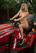 Outdoor photograph of a blond haired nude woman driving a red tractor