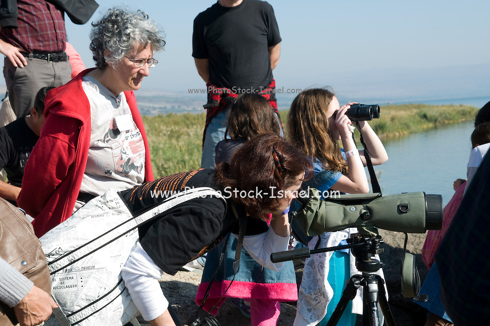 A group of people birdwatching. Photographed on the shores of the Sea of Galilee, Israel