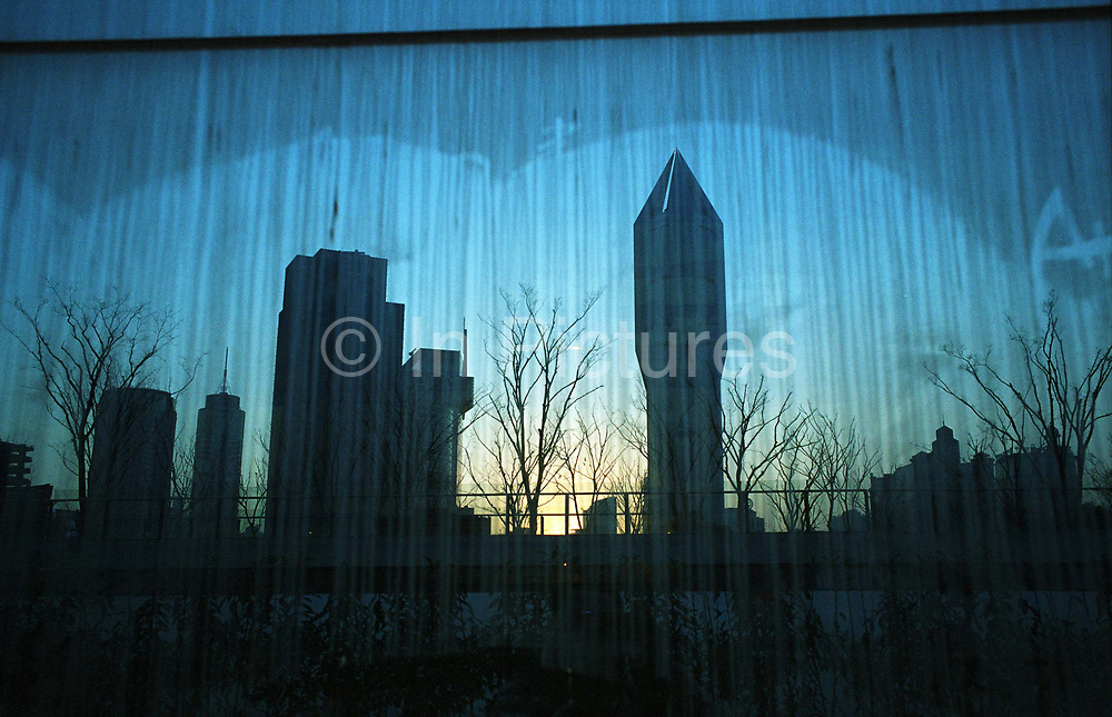 Image of downtown Shanghai, with the rocket-like Tomorrow square that houses the Marriott Hotel, is reflected in a glass panel in Shanghai.