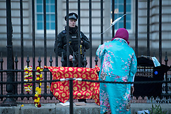 © Licensed to London News Pictures. 10/04/2021. London, UK. A police officer talk to a woman as she places a tribute at the gates of Buckingham Palace at first light, the morning after the death of Prince Philip, The Duke of Edinburgh. Yesterday (Fri) The British Royal Family announced the death of The Duke of Edinburgh, at the age of 99. Photo credit: Ben Cawthra/LNP