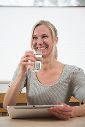 Woman with glass of water and digital tablet, smiling