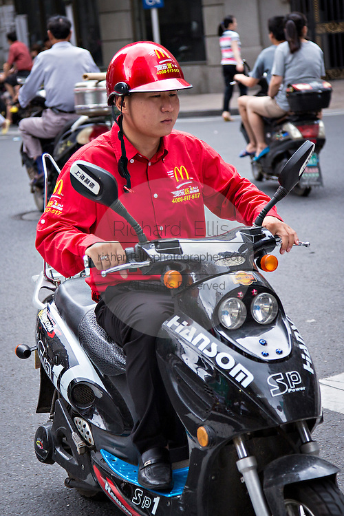 McDonald's delivery man rides a scooter in Shanghai, China.