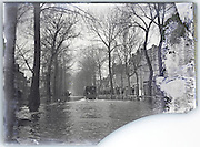 broken and eroding glass plate of flooded street with truck driving through the water , flood Seine River Paris January 1910