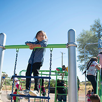 Caysie Largo, a student at Rehoboth Christian School plays on a hanging ladder in the new playground at Rehoboth following a dedication Tuesday morning. The playground was paid for by fundraising through the color runs and donations.