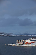 Scenic winter landscape with row of waterfront cabins against moody sky, Stokmarknes, Norway