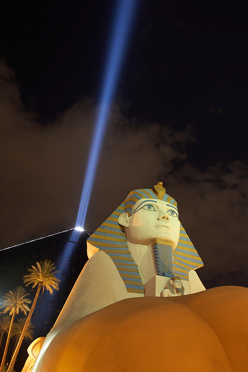 Nighttime view of the Luxor Hotel in Las Vegas with shaft of light emanating from the top of it's pyramid and sphinx in foreground
