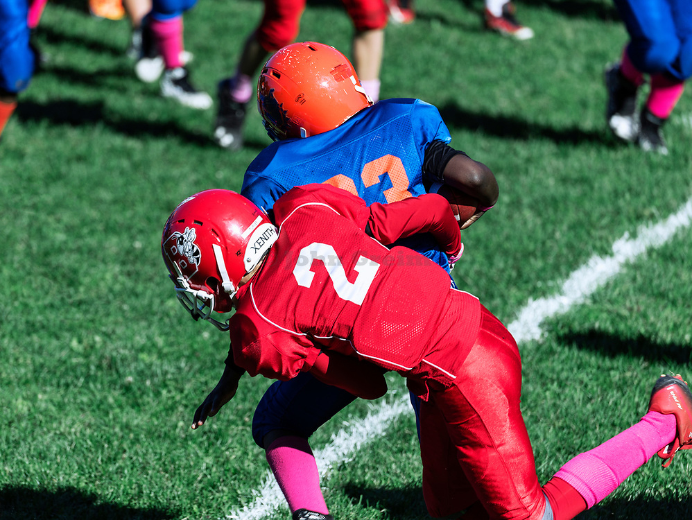 Making a tackle during a Pop Warner football game, USA