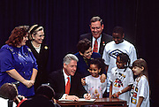 US President Bill Clinton signs a presidential decree on childcare as first lady Hillary Clinton and Health and Human Services Secretary Donna Shalala looks on at National Children's Hospital February 18, 1998 in Washington, DC.