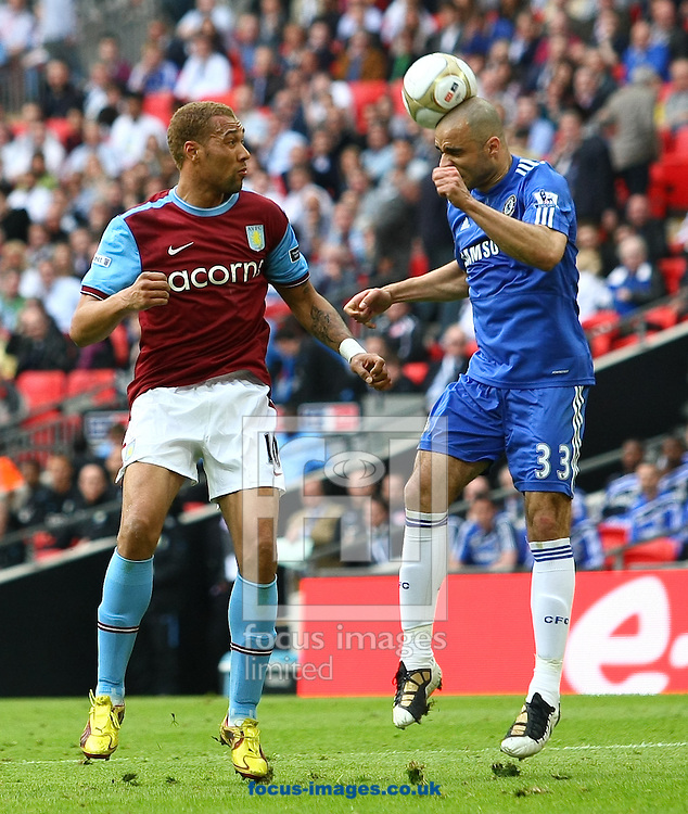London - Saturday April 10, 2010: Alex (33) of Chelsea heads the ball clear as John Carew (10) of Aston Villa looks on during the FA Cup semi final match between Aston Villa and Chelsea at Wembley Stadium, London. (Pic by Andrew Tobin/Focus Images)