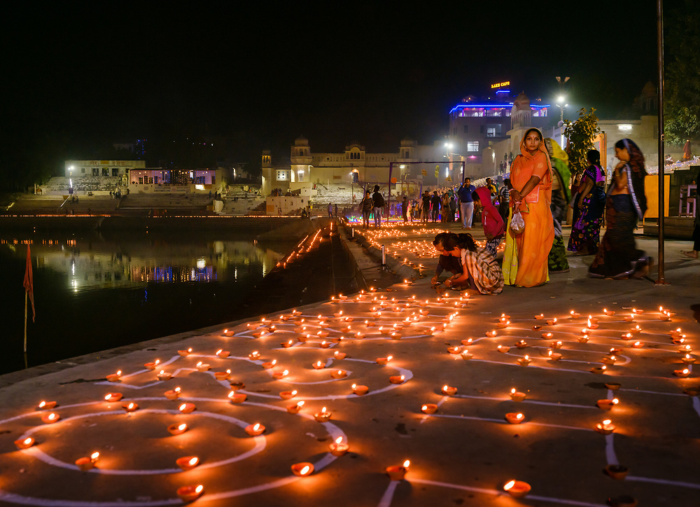 PUSHKAR, INDIA - CIRCA NOVEMBER 2018: People in the Pushkar Ghats during the opening ceremonies of the Camel Fair. It is one of the world's largest camel fairs. Apart from the buying and selling of livestock, it has become an important tourist destination. The city of Pushkar is a pilgrimage site for Hindus and Sikhs.