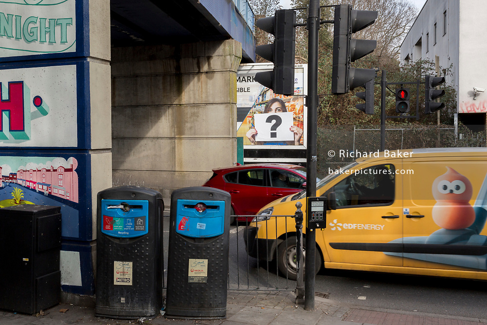 An EDF Energy van passes a question mark in the context of a billboard ad and traffic at East Dulwich, on 10th February 2019, in London, England.