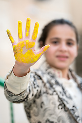 17 February 2020, Zarqa, Jordan: A girl shows her hand, yellow with paint, after painting her handmark on a wall of the Lutheran World Federation community centre in Zarqa. Through a variety of activities, the Lutheran World Federation community centre in Zarqa serves to offer psychosocial support and strengthen social cohesion between Syrian, Iraqi and other refugees in Jordan and their host communities.