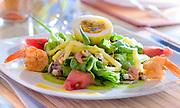 Photographie culinaire d'une salade composée posée sur une table de restaurant.