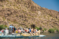 A big inflatable boat carries tourists through The Black Canyon, Nevada.