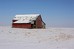 23 February 2008:  A dilapidated old red barn stands all alone on the prairie surrounded by the snow of winter and a bright blue sky.