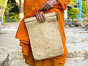 An elderly Buddhist monk wearing an orange robe holds an old Lao manuscript before a ceremony at the 480 year old temple in Ban Mouanghoun, Phongsaly province, Lao PDR. Although there are several villages with temples along the Nam Ou river, the remote and roadless Ban Mouanghoun is the only village in this area with its own resident monks who are also required to perform ceremonies at all the local villages. The village will be relocated due to the construction of the Nam Ou Cascade Hydropower project Dam 5.