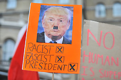 "© Licensed to London News Pictures. 17/03/2018. LONDON, UK.  A participant holds up an anti-Donald Trump sign.  People take part in a ""March against Racism"", walking from Portland Place to Downing Street, calling for a united movement for everyone against all forms of racism.  Photo credit: Stephen Chung/LNP"
