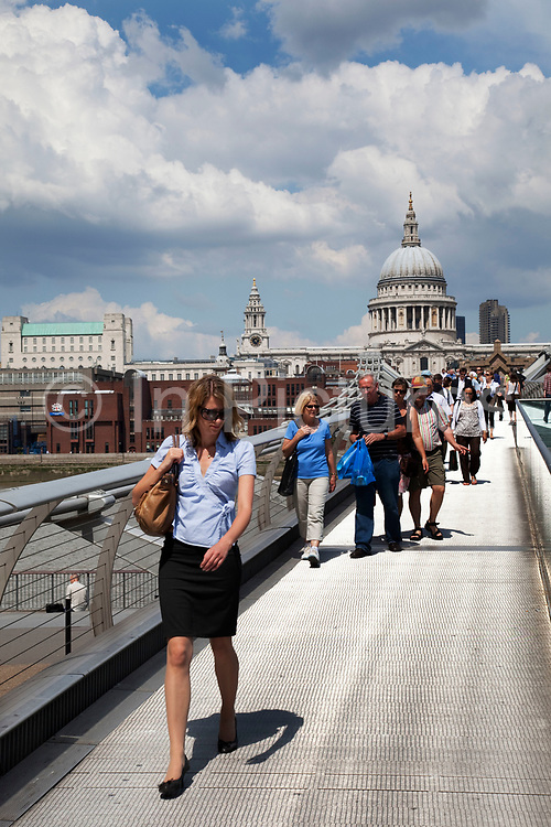People walk across the Millennium Bridge from St Pauls Cathedral towards Tate Modern on a sunny summer day. This bridge was affectinately called the wobbly bridge after it's fated construction and movement in the wond.