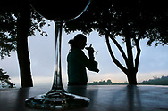 A young woman enjoying a glass of wine in the late afternoon, seen through the silhouette of a wine glass. Clouds Estate, South Africa.  The estate is located in the fertile Banhoek Valley located near the towns of Stellenbosch and Franschhoek and is visited by many tourists. (Model Released)