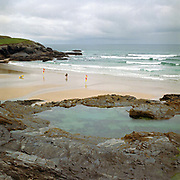 The Swimming Pool, Treyarnon Bay, Cornwall, UK. Until the 1950s and the rise of the heated indoor swimming pool, children learnt to swim outdoors. For those close to the sea, many man-made tidal swimming pools were constructed around Britain's coastline. Heated by the sun, these tidal pools were often built to keep bathers safe from high and rough seas, which explains why so many of them are clustered in Scotland and around the surfing beaches of Cornwall. Whether they are simple swimming holes made by shoring up natural rock pools or grand lido-like pools complete with lifeguards and tea huts, they are all refreshed by good high tides.