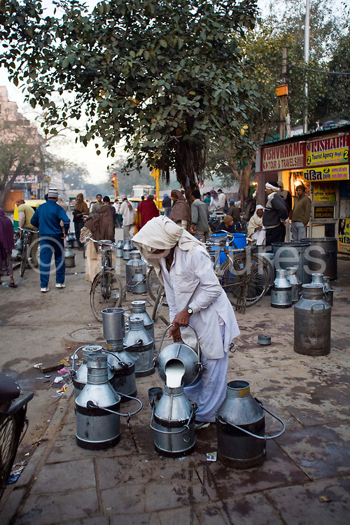A milkman pours milk into an churn at dawn in Old Delhi, India