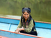 An Akha Nuquie ethnic minority woman sits in a local boat waiting to travel along the Nam Ou river to the her home in the roadless village of Phou-Yot, three hours walk from the river, Phongsaly province, Lao PDR