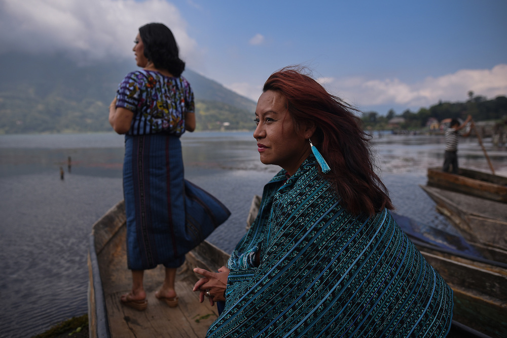 """Portrait of Maria Alejandra and Kristel, two transgender women of indigenous origin Tz'utujil, observe Lake Atitlan during a sunny day. November 20, 2019 in Santiago Atitlán, Guatemala. The story of Maria Alejandra """"La China"""", and Kristel two indigenous trans women of Tz'utujil origin, has been forged by love, understanding and complicity. From a very young age they found in the community of Santiago, Atitlán, in Guatemala, where they began to discover their identity. Supporting each other they realized their preferences and similarities. In October 2019 in Guatemala, the observatory of violent deaths from sexual orientation and gender identity, recorded 15 murders of transgender women that year."""