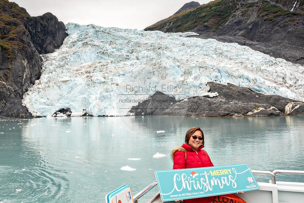 A Philippine tourist poses in front of Coxe Glacier, a tidewater glacier in Barry Arm, Harriman Fjord, Prince William Sound near Whittier, Alaska.