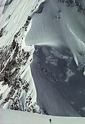 Skier on Central Rongbuk glacierclimbs towards base of West Ridge under North face Chomolungma , Mt Everest, Tibet