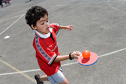 Boy taking part in sports day competition in school playground,