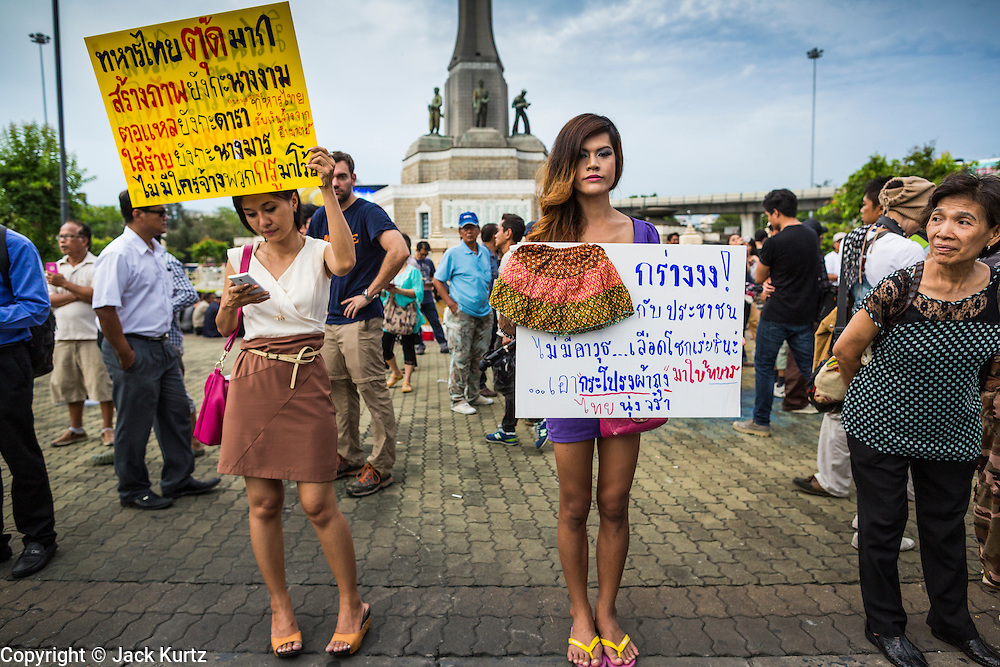"""27 MAY 2014 - BANGKOK, THAILAND: Two women and a """"katoey"""" or ladyboy, at Victory Monument in Bangkok protest against the coup. Several hundred people protested against the coup in Bangkok at Victory Monument. It was the fourth straight day of pro-democracy rallies in the Thai capital as the army continued to tighten its grip on Thai life. The protest Tuesday was the smallest so far.     PHOTO BY JACK KURTZ"""
