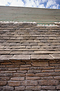 Re-roofing with reproduction Cotswold roof slates of a Cotswolds stone cottage using traditional method of tiling, UK
