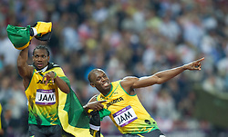 © Licensed to London News Pictures. 11/08/2012. London,UK. Usain Bolt, Yohan Blake, Nesta Carter and Michael Frater of Jamaica pose next to the clock showing the new World Record after Jamaica won the men's 4x100m final at the London 2012 Olympic Games Athletics, Track and Field events at the Olympic Stadium, London, Britain, 11 August 2012..  Photo credit : Bogdan Maran/LNP/BPA