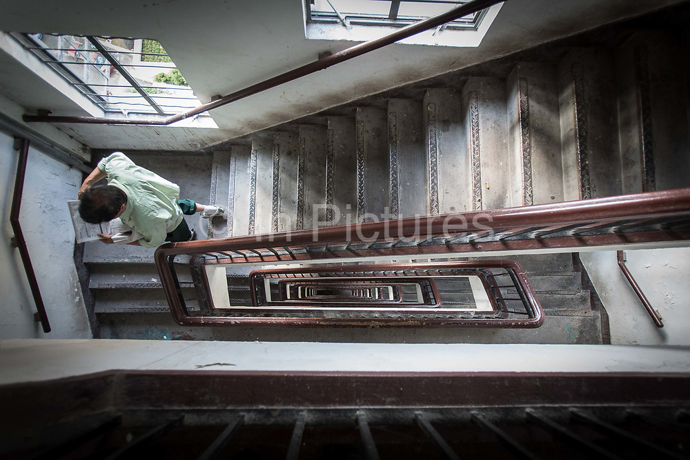 A man walks down a flight of stairs at Sir Victor Sassoons Embankment House in Shanghai, China on September 21, 2014. Sassoon was a jewish tycoon that left a series of buildings that once dominated the city of Shanghai in the 1920s and 30s.