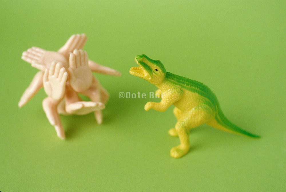 toy dinosaur and hands