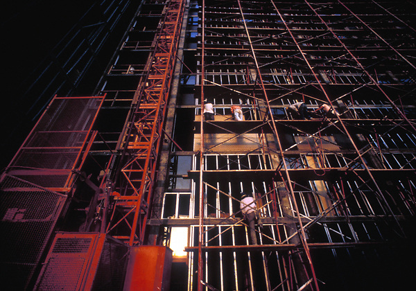 Stock photo of men on scaffolding fixed to a large building