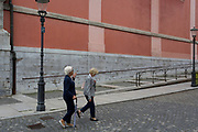 Two ladies walk up Miklosiceva Cesta (street) in the Slovenian capital, Ljubljana, on 28th June 2018, in Ljubljana, Slovenia.