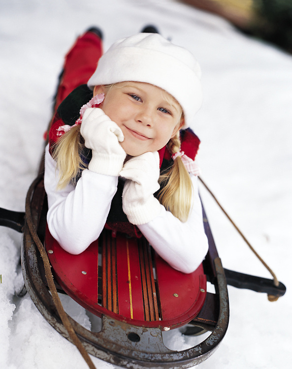 A young girl lies on a rustic red wooden sled. This photo was created in the summer in South Florida. We produced this image by laying down real snow in Florida.