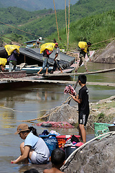 Labourers work to unload a Cargo river boat carrying fertilizer on the River Mekong in the early morning.  Pak Beng, Oudomxay Province, Lao PDR